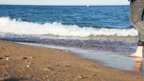 Ξυπόλυτο κορίτσι που περπατά κατά μήκος μιας αμμώδους παραλίας φιλμ μικρού μήκους