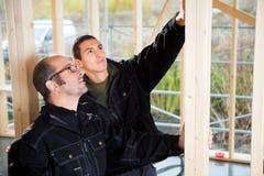 Ξυλουργοί που εξετάζουν το ξύλο στο ελλιπές κτήριο Στοκ φωτογραφία με δικαίωμα ελεύθερης χρήσης