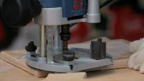 Ξυλουργός εργασίας με μια ηλεκτρική χέρι-άλεση απόθεμα βίντεο