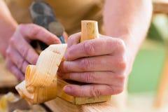 Ξυλουργός με την ξύλινη μηχανή πλανίσματος και κομμάτι προς κατεργασία στην ξυλουργική στοκ εικόνες με δικαίωμα ελεύθερης χρήσης