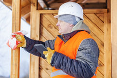 Ξυλουργός με το PC ταμπλετών κοντά στο ξύλινο κτήριο Στοκ Φωτογραφίες