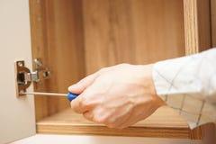 Ξυλουργός που εγκαθιστά την άρθρωση πορτών επίπλων και που χρησιμοποιεί το κατσαβίδι στοκ φωτογραφία
