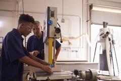 Ξυλουργός που εκπαιδεύει τον αρσενικό μαθητευόμενο μηχανοποιημένο στο χρήση πριόνι Στοκ Εικόνες