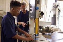 Ξυλουργός που εκπαιδεύει τον αρσενικό μαθητευόμενο μηχανοποιημένο στο χρήση πριόνι Στοκ εικόνες με δικαίωμα ελεύθερης χρήσης