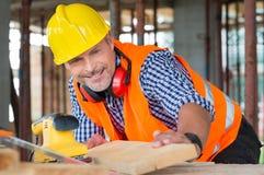 Ξυλουργός που εξετάζει τη σανίδα Στοκ φωτογραφία με δικαίωμα ελεύθερης χρήσης