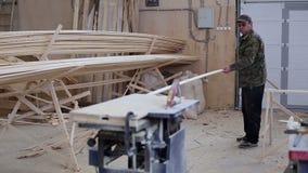 Ξυλουργός που εργάζεται με την κυκλική μηχανή ξυλουργικής πριονιών φιλμ μικρού μήκους