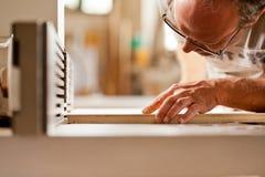 Ξυλουργός που ελέγχει τον πίνακα σε έναν ξύλινο διαμορφωτή Στοκ φωτογραφία με δικαίωμα ελεύθερης χρήσης