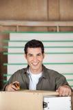 Ξυλουργός που μετρά το γραφείο με την ταινία Στοκ Εικόνες