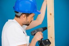 Ξυλουργός που τρυπά μια τρύπα σε μια σανίδα του ξύλου με τρυπάνι Στοκ Εικόνες