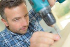 Ξυλουργός που τρυπά προσεκτικά την τρύπα με τρυπάνι Στοκ φωτογραφία με δικαίωμα ελεύθερης χρήσης