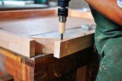 Ξυλουργός που τρυπά το πλαίσιο πορτών με τρυπάνι στοκ εικόνες