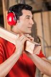 Ξυλουργός που φέρνει την ξύλινη σανίδα στον ώμο Στοκ Εικόνες