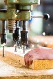 Ξυλουργός που χρησιμοποιεί το ηλεκτρικό τρυπάνι στην ξυλουργική στοκ φωτογραφίες