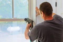 Ξυλουργός που χρησιμοποιεί το πυροβόλο όπλο καρφιών στις σχηματοποιήσεις στα παράθυρα, που πλαισιώνουν την περιποίηση, Στοκ Εικόνες