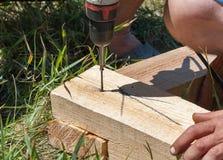 Ξυλουργός που χρησιμοποιεί το τρυπάνι και τη βίδα ξύλινο σε υπαίθριο Στοκ Εικόνες