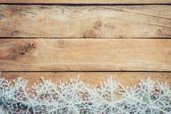 Ξύλινα καφετιά υπόβαθρο και snowflakes Χριστουγέννων με το διάστημα Στοκ Φωτογραφίες