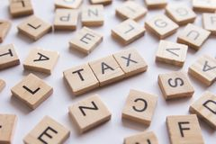 Ξύλινα κεραμίδια φραγμών επιστολών αλφάβητου Φορολογικό κείμενο στην ΤΣΕ της Λευκής Βίβλου στοκ φωτογραφία