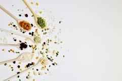 Ξύλινα κουτάλια στη αριστερή πλευρά, πλήρη των σπόρων και των δημητριακών στοκ φωτογραφία