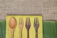 Ξύλινα κουτάλι και δίκρανα σχεδίου στην κίτρινη πετσέτα πέρα από το πράσινο φύλλο μπανανών Στοκ Εικόνες