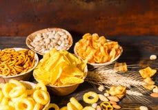 Ξύλινα πιάτα με τα πρόχειρα φαγητά κοντά στο σίτο, τα διεσπαρμένα καρύδια και pretzel Στοκ εικόνες με δικαίωμα ελεύθερης χρήσης