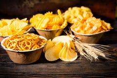 Ξύλινα πιάτα με τα πρόχειρα φαγητά κοντά στο σίτο, διεσπαρμένα τσιπ στο σκοτεινό wo Στοκ Φωτογραφίες