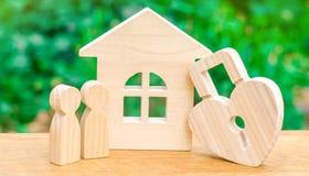 Ξύλινα σπίτι και λουκέτο με μορφή μιας καρδιάς σε ένα πράσινο υπόβαθρο Η έννοια μιας φωλιάς αγάπης που αγοράζει ένα σπίτι ή ένα δ στοκ φωτογραφίες