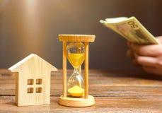 Ξύλινα σπίτι και ρολόι Μετρώντας χρήματα επιχειρηματιών Πληρωμή της κατάθεσης ή προκαταβολή για την ενοικίαση ενός σπιτιού ή ενός στοκ φωτογραφίες με δικαίωμα ελεύθερης χρήσης