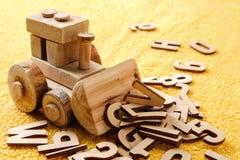 Ξύλινες επιστολές αλφάβητου με το παιχνίδι Εκπαιδευτική έννοια στο κίτρινο υπόβαθρο Στοκ Εικόνα