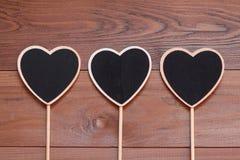 Ξύλινες καρδιές πινάκων κιμωλίας σε ένα μακρύ ραβδί για το κείμενο Στοκ Φωτογραφία