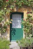 Ξύλινες πόρτες στο εξοχικό σπίτι Cotswolds με την ένωση των τριαντάφυλλων στοκ εικόνα