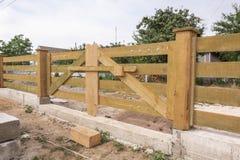Ξύλινες πύλες για την είσοδο οχημάτων μέσα σε το σπίτι Φράκτης στο ύφος αγροκτημάτων στοκ φωτογραφία με δικαίωμα ελεύθερης χρήσης