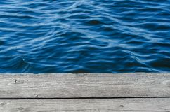 Ξύλινες σανίδες, λιμενοβραχίονας στην ακτή, μπλε νερό, κύματα στοκ εικόνες