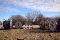Ξύλινες σπείρες με τα βιομηχανικά καλώδια σε έναν τομέα στοκ εικόνες