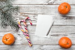 Ξύλινη ανασκόπηση άσπρος Χειμερινή ευχετήρια κάρτα Το FIR πράσινο Πορτοκάλια Δώρα καραμέλες ζωηρόχρωμες Στοκ Φωτογραφία