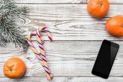Ξύλινη ανασκόπηση άσπρος Χειμερινή κάρτα Κλάδος του FIR πράσινος Πορτοκάλια Κινητό τηλέφωνο καραμέλες ζωηρόχρωμες Στοκ Εικόνες