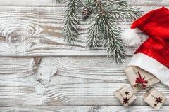 Ξύλινη ανασκόπηση άσπρος Χειμερινή κάρτα Το καπέλο Santa του ` s Το δέντρο έλατου Διάστημα για τη ευχετήρια κάρτα με τα Χριστούγε Στοκ εικόνα με δικαίωμα ελεύθερης χρήσης