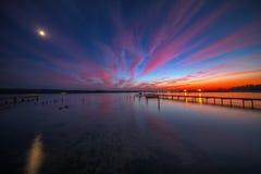 Ξύλινη αποβάθρα και αλιευτικό σκάφος στη λίμνη, πυροβολισμός ηλιοβασιλέματος Στοκ Εικόνες