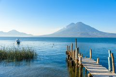 Ξύλινη αποβάθρα στη λίμνη Atitlan στην ακτή σε Panajachel, Γουατεμάλα Με το όμορφο τοπίο τοπίων των ηφαιστείων Toliman, Atitlan στοκ φωτογραφία με δικαίωμα ελεύθερης χρήσης