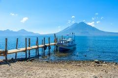 Ξύλινη αποβάθρα στη λίμνη Atitlan στην παραλία σε Panajachel, Γουατεμάλα Με το όμορφο τοπίο τοπίων των ηφαιστείων Toliman, Atitla στοκ εικόνα