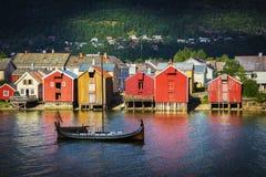 Ξύλινη βάρκα σε έναν ποταμό, ζωηρόχρωμα λιμενικά κτήρια στοκ φωτογραφία με δικαίωμα ελεύθερης χρήσης