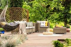 Ξύλινη βεράντα με τα έπιπλα ινδικού καλάμου, τη comfy ταλάντευση και τα δέντρα στο τ στοκ εικόνα