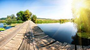 Ξύλινη γέφυρα πέρα από τον ποταμό με τα πράσινα δέντρα κάτω από το φωτεινό ήλιο Στοκ εικόνα με δικαίωμα ελεύθερης χρήσης