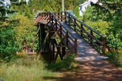 Ξύλινη γέφυρα πέρα από το ρεύμα στη δασική, ξύλινη διακοσμητική γέφυρα για τους τουρίστες Στοκ Φωτογραφίες