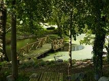 Ξύλινη γέφυρα σε μια πράσινη λίμνη χαλάρωσης σε έναν κήπο Στοκ Εικόνες
