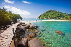 Ξύλινη γέφυρα στον καφετή βράχο και όμορφο θαλάσσιο νερό παραλιών άμμου σαφούς και στο nang yuan koh στο tao Ταϊλάνδη στα όμορφα  στοκ φωτογραφία