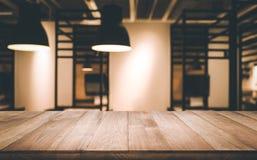 Ξύλινη επιτραπέζια κορυφή θολωμένος του εσωτερικού δωματίων με τη λάμπα φωτός Στοκ Εικόνα