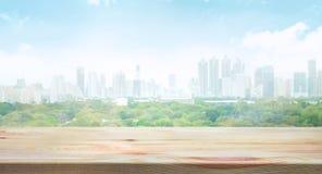 Ξύλινη επιτραπέζια κορυφή θολωμένος του υποβάθρου άποψης πόλεων στοκ εικόνα