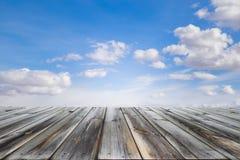 Ξύλινη επιτραπέζια κορυφή με το μπλε ουρανό και τα άσπρα σύννεφα Διάστημα για το παρόν ένα προϊόν στοκ φωτογραφίες