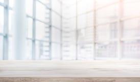 Ξύλινη επιτραπέζια κορυφή στο άσπρο γραφείο μορφής υποβάθρου παραθύρων γυαλιού θαμπάδων στοκ φωτογραφία