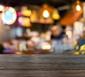 Ξύλινη επιτραπέζια κορυφή στο θολωμένο αντίθετο φραγμό σκηνής στη καφετερία Στοκ Εικόνα
